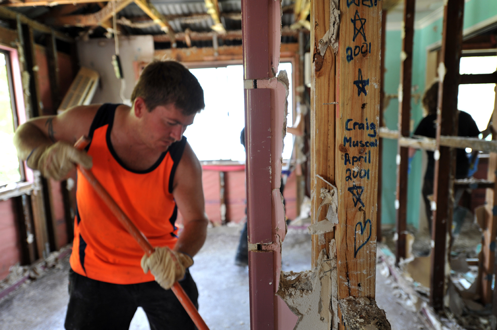 Global Care Volunteer Reg Potter of Oak Flats, sweeps debris around the framework of a house in North Booval, Queensland.