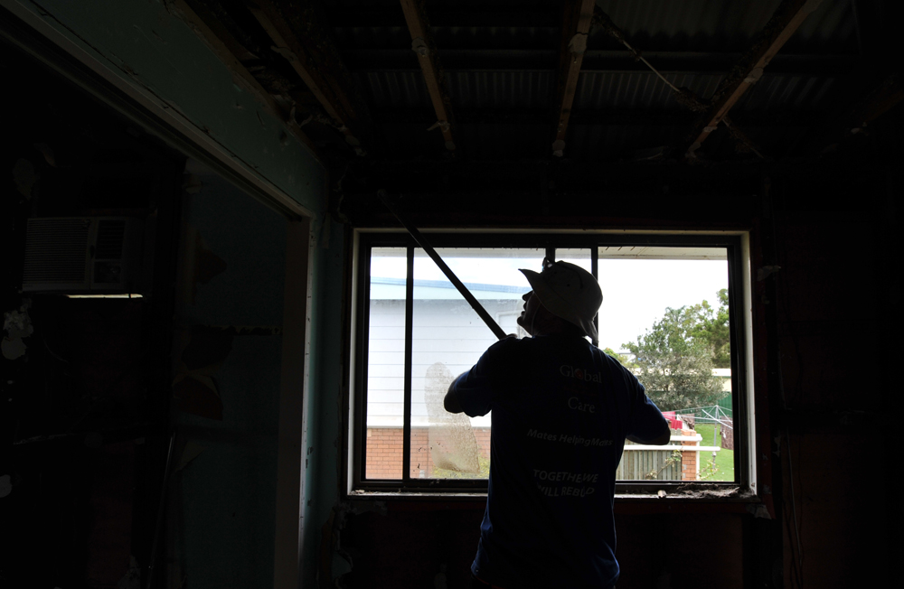 Global Care Volunteer Reg Potter uses a shovel to bring down loose gyprock in a house in North Booval, Queensland.
