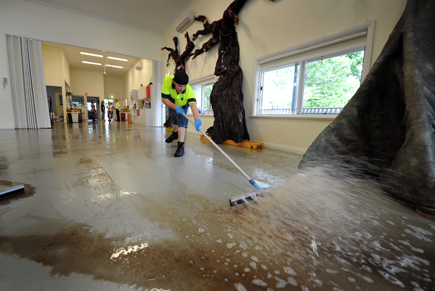 Council Waste Services staff Ryan Sellars helps clean out the floodwaters from the Jamberoo Preschool.