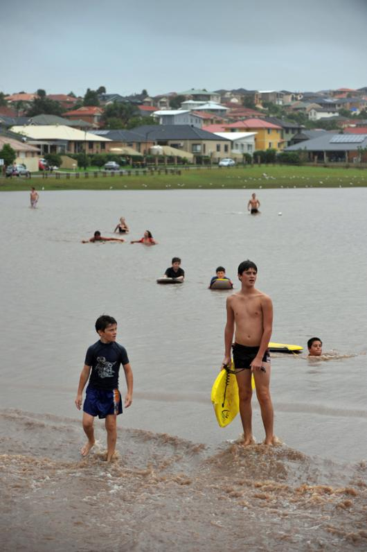 Youth frolick with body boards in the floodwaters across Flinders sporting field during flash flooding across the Illawarra region.