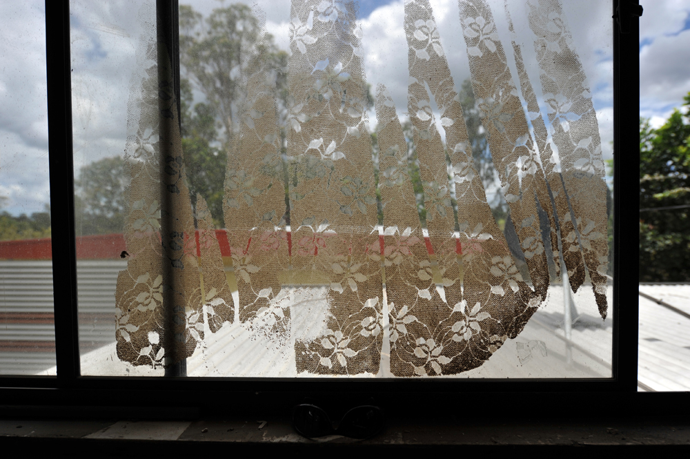The pattern of a lace curtain is printed onto a glass window as mud residue dries in a house in North Booval, Queensland.