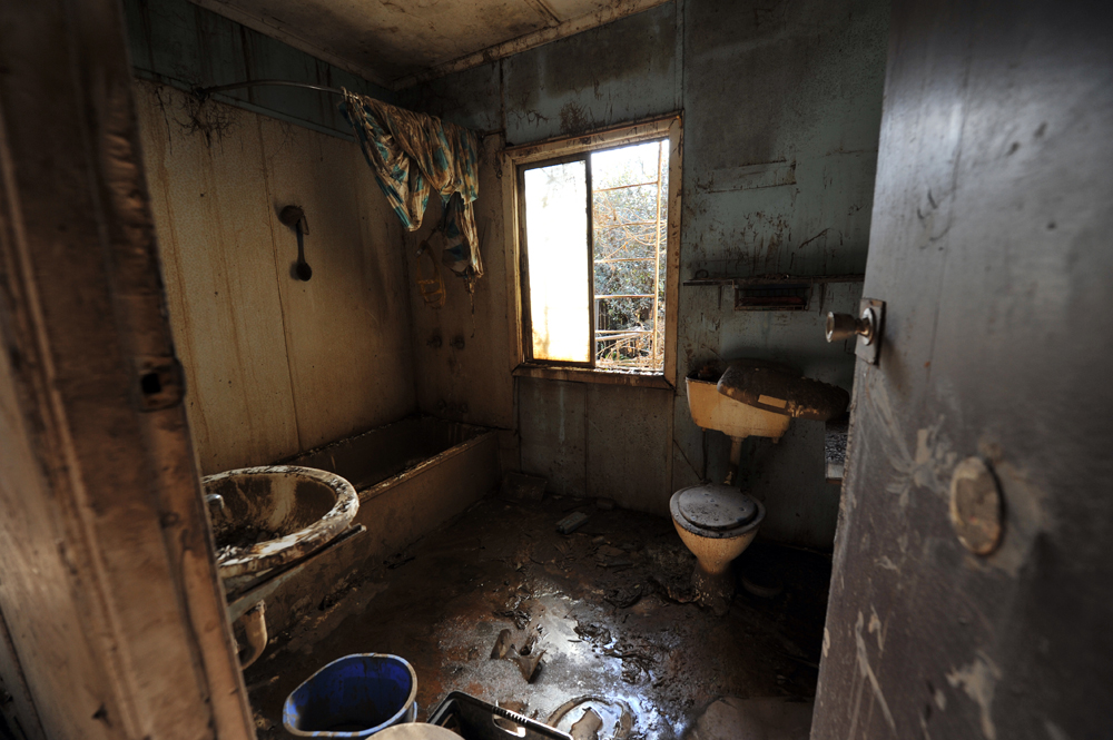 Faeces and mud cover a bathroom from floor to ceiling in Goodna, Queensland.