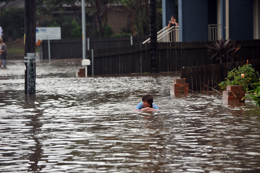 Flood water crosses the intersection of George Street and Susan Ave, Warilla, during flash flooding across the Illawarra region.